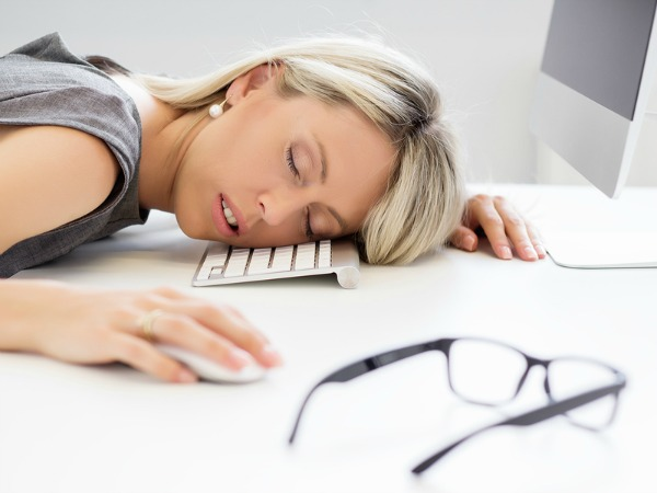 Exhausted business woman sleeping in front of computer